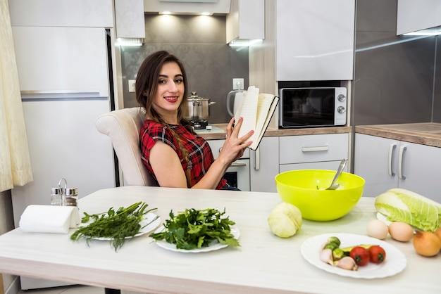 若いきれいな女性は、さまざまな野菜を持って台所のテーブルに座って、健康的な栄養についてのすべてを日記に書いたり書いたりします