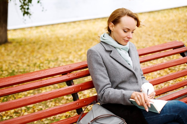 Young pretty woman sitting on a bench in autumn park with a notebook and coffee