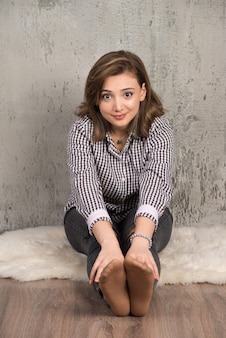 Giovane bella donna seduta sul pavimento e guardando la parte anteriore