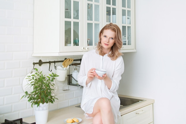 차 한잔과 함께 부엌에 앉아 젊은 예쁜 여자, 라이프 스타일