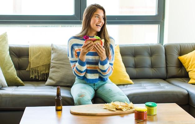 Молодая красивая женщина, сидящая на кожаном диване, ест
