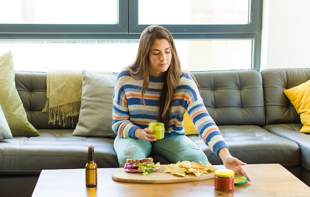 食べる革のソファに座っている若いきれいな女性