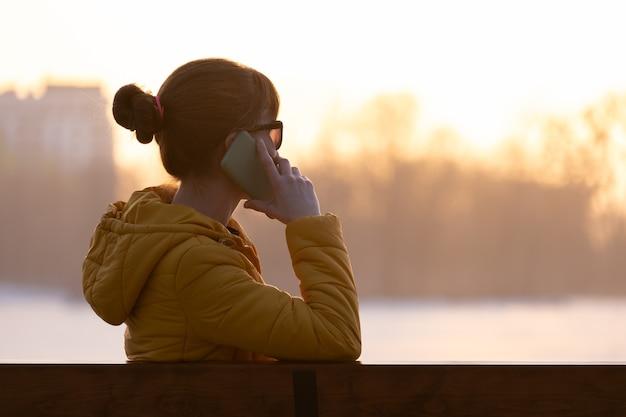 공원 벤치에 앉아 야외에서 스마트폰으로 이야기하는 젊은 예쁜 여자