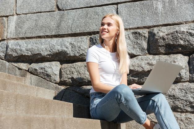 ラップトップコンピューターで階段に座っている若いきれいな女性