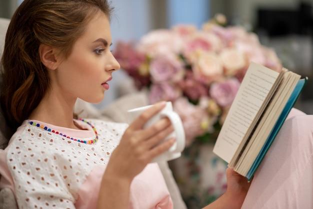 コーヒーを飲みながら本を読んでソファに座っている若いきれいな女性は休息を楽しんでいます