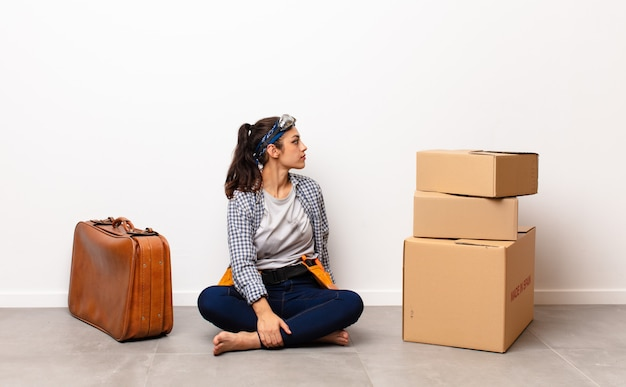 Young pretty woman sitting with boxes and a suitcase