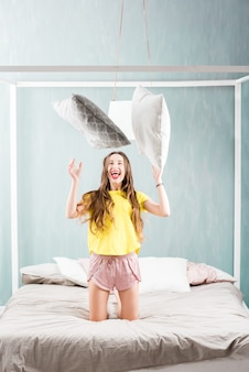 Young pretty woman in sleepwear playing with pillows in the bedroom