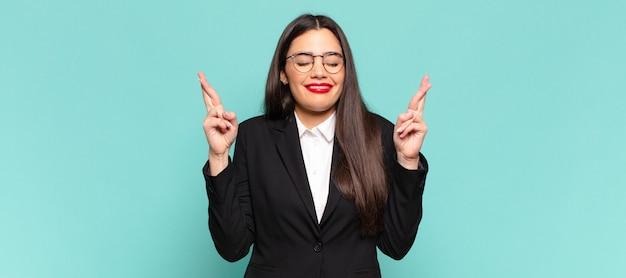 젊고 예쁜 여자는 웃으면서 걱정스럽게 두 손가락을 교차시키며 걱정하고 행운을 빌거나 바라고 있습니다. 비즈니스 개념