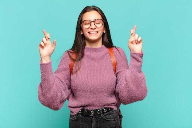 젊고 예쁜 여자는 웃으면서 걱정스럽게 두 손가락을 교차시키며 걱정하고 행운을 빌거나 바라고 있습니다. 학생 개념