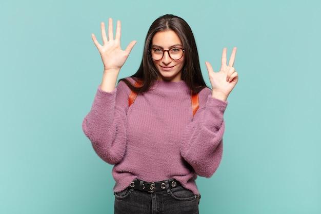 젊은 예쁜 여자 웃 고 친절 하 게 찾고, 앞으로 카운트 다운, 손으로 8 또는 8 번째 표시. 학생 개념