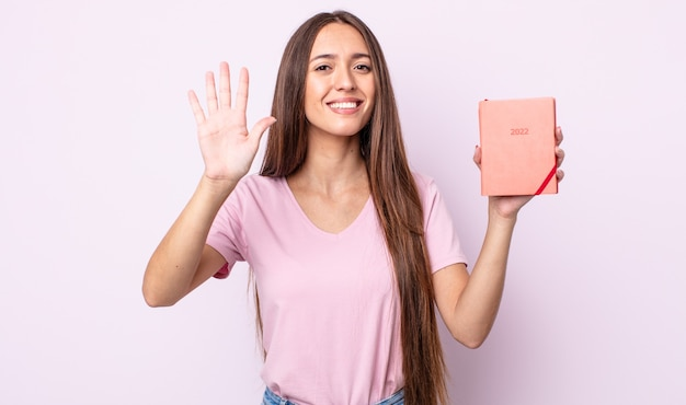 Молодая красивая женщина улыбается и выглядит дружелюбно, показывая номер пять. концепция планировщика 2022 года