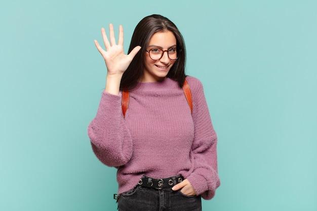 Молодая симпатичная женщина улыбается и выглядит дружелюбно, показывает номер пять или пятое с рукой вперед, отсчитывая. студенческая концепция