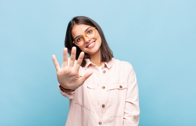 젊은 예쁜 여자가 미소하고 친절하게보고, 앞으로 손으로 5 번 또는 5 번을 보여주는, 카운트 다운
