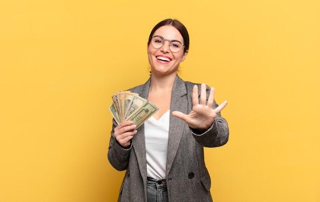 Молодая красивая женщина улыбается и выглядит дружелюбно, показывает номер пять или пятое с рукой вперед, отсчитывая