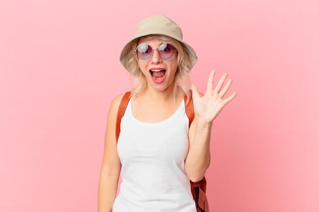 笑顔でフレンドリーに見える若いきれいな女性は、5番目を示しています。夏の観光コンセプト