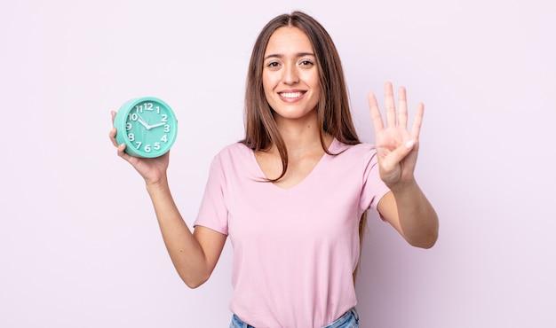 Молодая красивая женщина улыбается и выглядит дружелюбно, показывая номер четыре. концепция будильника