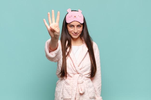 Молодая красивая женщина улыбается и выглядит дружелюбно, показывает номер четыре или четвертый с рукой вперед, отсчитывая