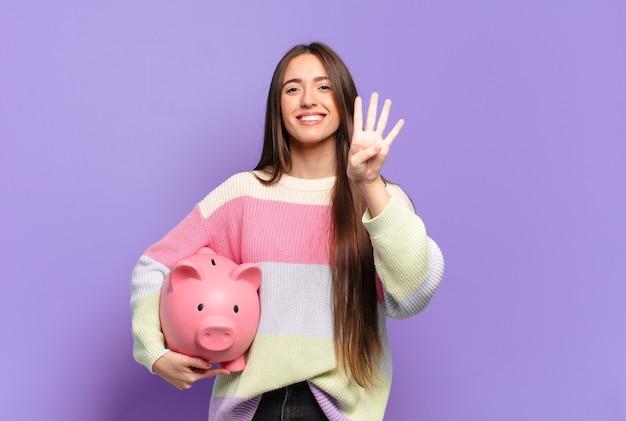 Молодая симпатичная женщина улыбается и выглядит дружелюбно, показывает номер четыре или четвертый с рукой вперед, отсчитывая