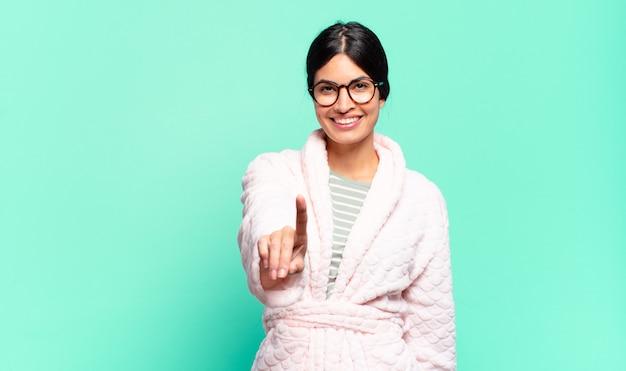 젊은 예쁜 여자 웃 고 친절 하 게 찾고, 숫자 하나 또는 손으로 앞으로 표시, 카운트 다운. 잠옷 컨셉