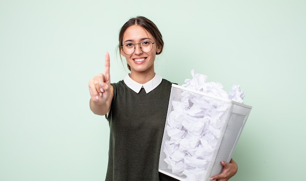 若いきれいな女性は笑顔でフレンドリーに見え、ナンバーワンを示しています。紙球ゴミ箱の概念