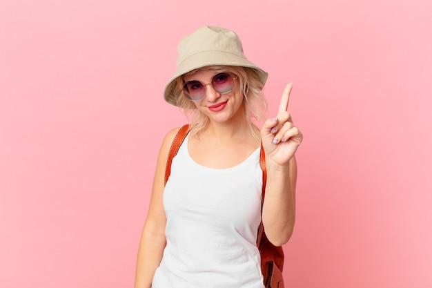 笑顔でフレンドリーに見える若いきれいな女性は、ナンバーワンを示しています。夏の観光コンセプト