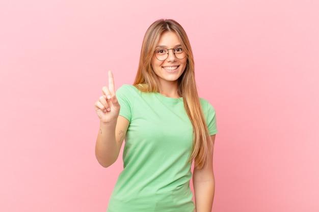 笑顔でフレンドリーに見える若いきれいな女性、ナンバーワンを示しています