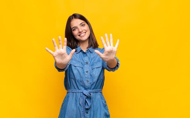 젊은 예쁜 여자가 미소하고 친절하게보고, 앞으로 손으로 숫자 10 또는 10을 보여주는, 카운트 다운