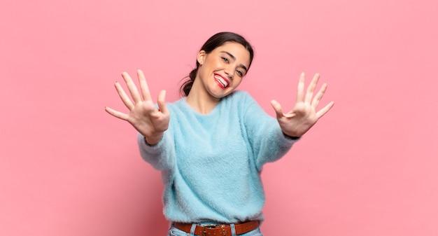 Молодая симпатичная женщина улыбается и выглядит дружелюбно, показывает десятую или десятую руку вперед, отсчитывая