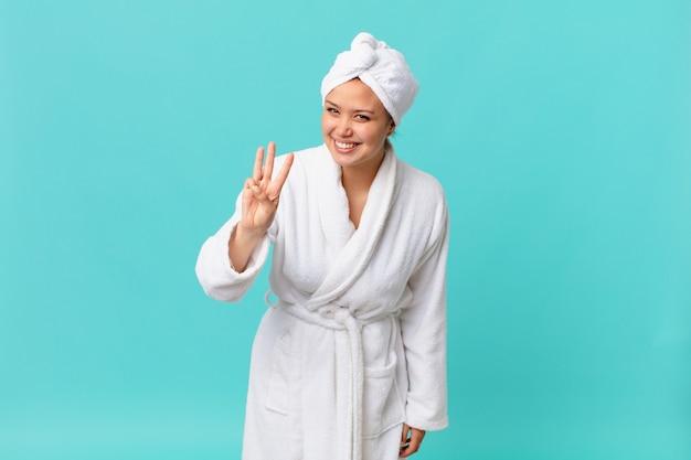 Молодая красивая женщина улыбается и выглядит дружелюбно, показывает номер три и в купальном халате после душа