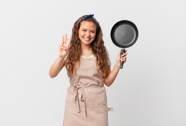 Молодая красивая женщина улыбается и выглядит дружелюбно, показывает концепцию шеф-повара номер три и держит сковороду