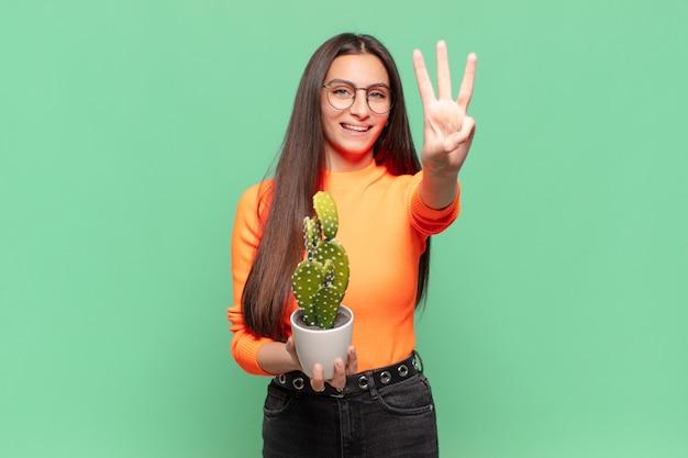 若いきれいな女性は笑顔でフレンドリーに見え、前に手を出して3番目または3番目を示し、カウントダウンします。サボテンの概念