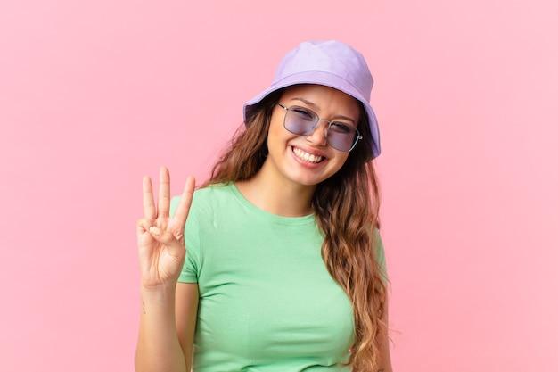 笑顔でフレンドリーに見える若いきれいな女性は、3番目を示しています。夏のコンセプト