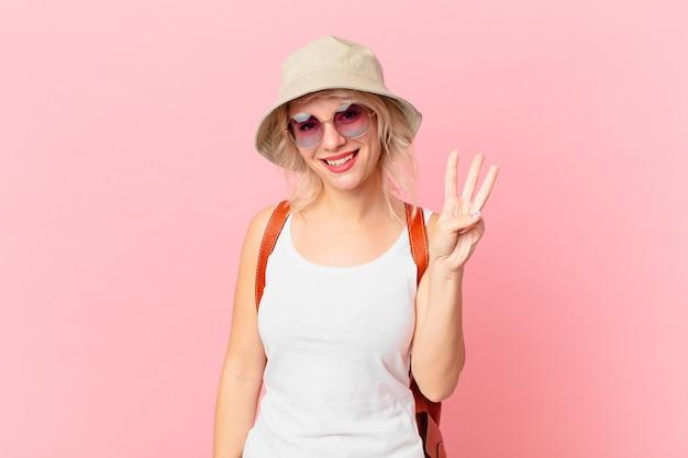 笑顔でフレンドリーに見える若いきれいな女性は、3番目を示しています。夏の観光コンセプト