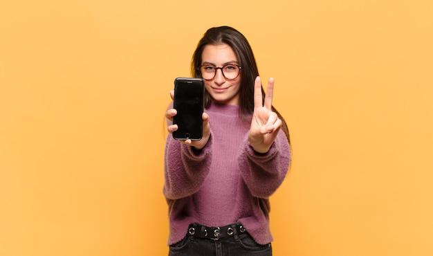 Молодая красивая женщина улыбается и выглядит дружелюбно, показывая номер два или секунду рукой вперед, отсчитывая. концепция экрана телефона Premium Фотографии