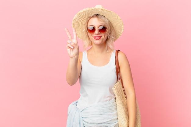 若いきれいな女性は笑顔でフレンドリーに見え、2番目を示しています。夏の観光コンセプト