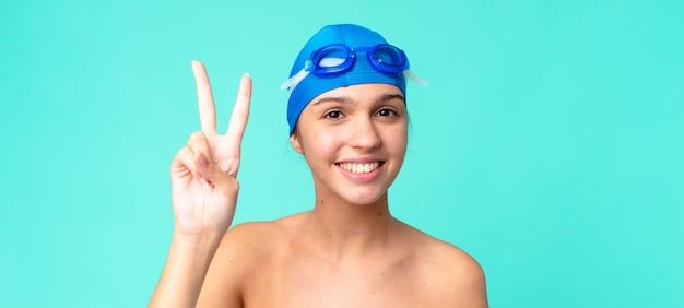 Молодая красивая женщина улыбается и выглядит дружелюбно, показывая номер два в плавательных очках