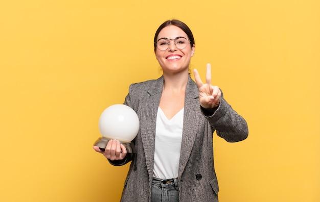 笑顔で幸せそうに見える若いきれいな女性、のんきで前向きで、片手で勝利または平和を身振りで示す