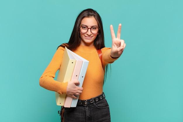 Молодая красивая женщина улыбается и выглядит счастливой, беззаботной и позитивной, жестикулируя победу или мир одной рукой