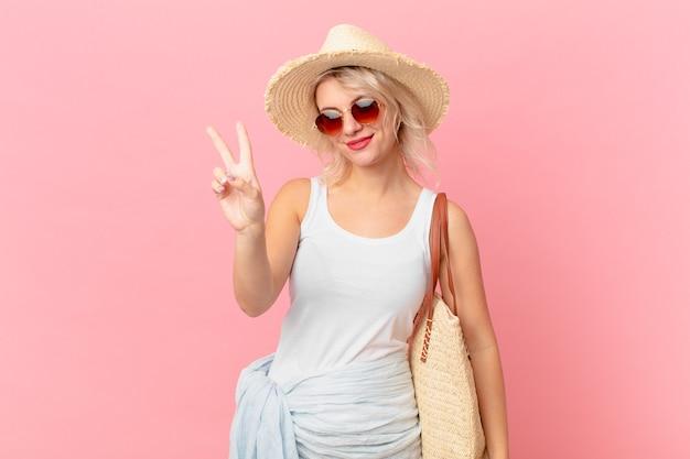 笑顔と幸せそうに見える、勝利または平和を身振りで示す若いきれいな女性。夏の観光コンセプト