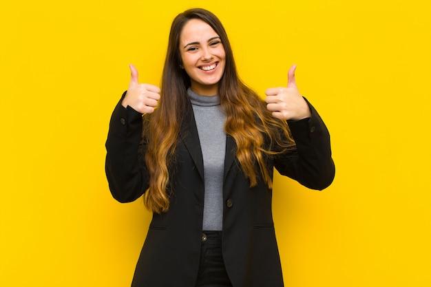 仕事やビジネスの概念を両方親指で広く見て幸せ、肯定的、自信を持って、成功した笑顔若いきれいな女性
