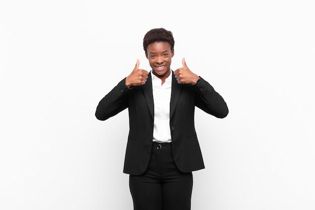 白い壁を越えて両方の親指で広く見て幸せ、肯定的、自信を持って成功した笑顔の若いきれいな女性