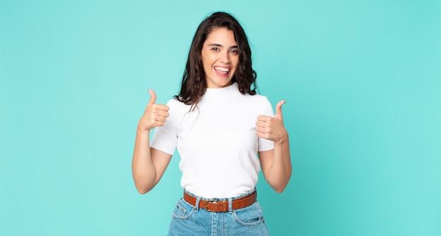 Молодая красивая женщина широко улыбается, выглядит счастливой, позитивной, уверенной и успешной, с двумя пальцами вверх