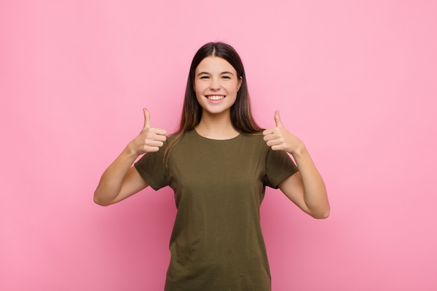 Young pretty woman smiling broadly looking happy, positive, confident and successful, with both thumbs up against pink wall