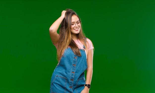 緑の壁に前向きで幸せで自信を持って顔を合わせて頭を元気に、カジュアルに笑っている若いきれいな女性