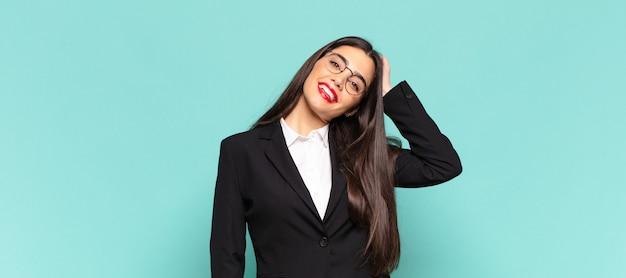 Молодая красивая женщина весело и небрежно улыбается, взявшись за голову с позитивным, счастливым и уверенным взглядом. бизнес-концепция