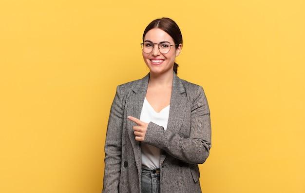 元気に笑って、幸せを感じて、横と上を指して、コピースペースでオブジェクトを示す若いきれいな女性