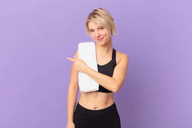 Молодая красивая женщина весело улыбается, чувствуя себя счастливой и указывая в сторону. фитнес-концепция