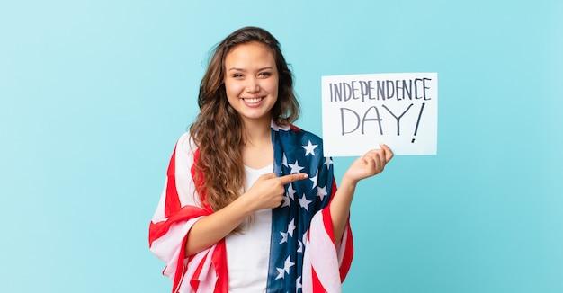元気に笑って、幸せを感じて、サイド独立記念日のコンセプトを指している若いきれいな女性