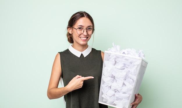 元気に笑って、幸せを感じて、横を指している若いきれいな女性。紙球ゴミ箱の概念