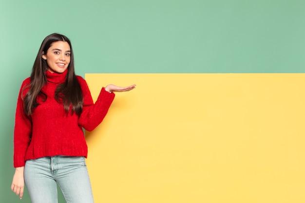 유쾌 하 게 웃 고, 행복 한 느낌과 손바닥으로 복사 공간에 개념을 보여주는 젊은 예쁜 여자. 개념을 배치 할 공간 복사